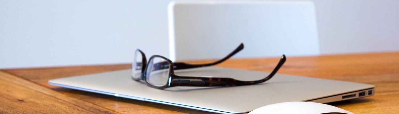 Foto von einem Tisch mit Notebook und Brille