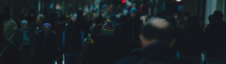 Menschenmenge in einer Fußgängerzone am Abend