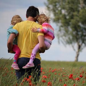 Ein Vater trägt zwei Kinder durch ein Sommerfeld. |Der Kreis der Väter in Köln
